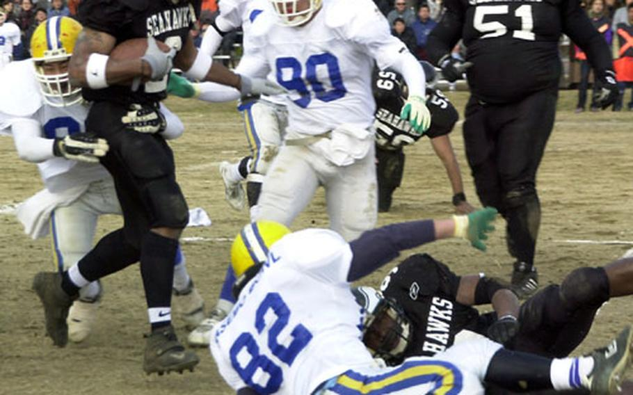 Chris Bolden (2), a runningback for the Yokosuka Seahawks, tries to avoid tripping over a downed blocker and his victim during a dash for a big gain on Saturday during the Sasebo Bowl.
