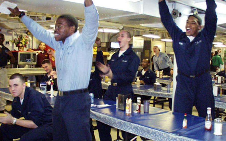 Airman Maurice Reid, left, and Airman Albert Crews celebrate early Monday morning in the mess decks aboard the USS Harry S. Truman as Tampa Bay wins the Super Bowl.