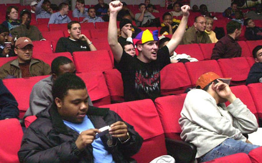 Football fans at Sasebo Naval Base cheer their teams during the Super Bowl on Monday morning. The game was shown on the movie screen at the base's Showboat Theater.