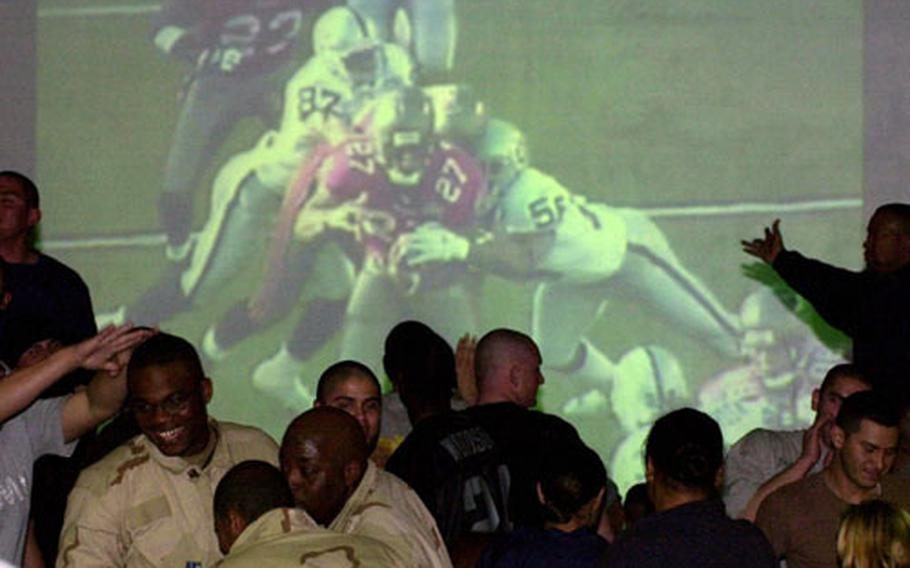 Soldiers at Camp Doha react to the action during Super Bowl XXXVII, broadcast on a big-screen at a former warehouse turned into the base club.