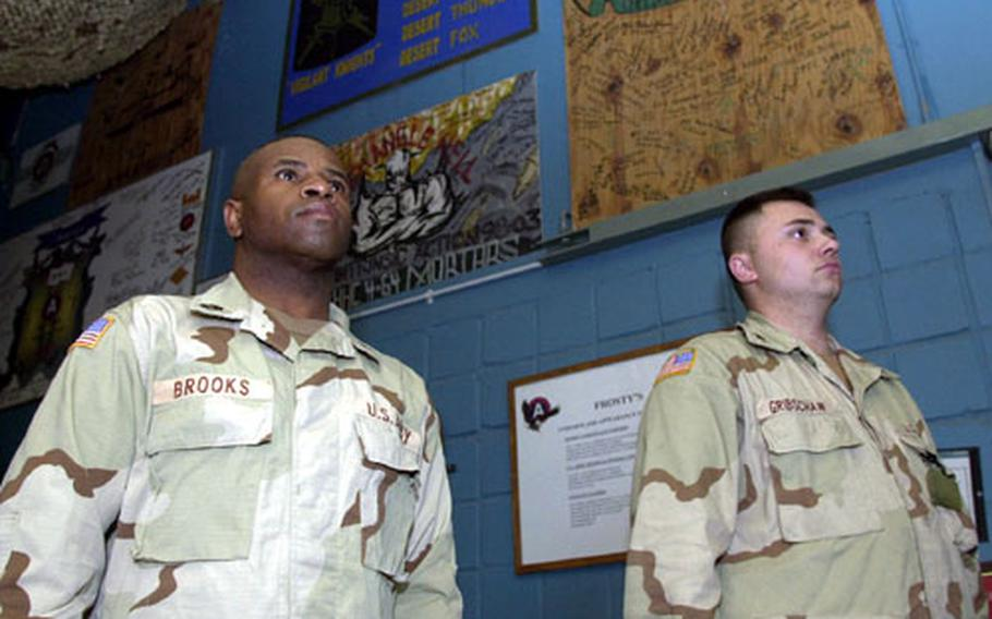 Sgt. First Class Terry Brooks (left), of Lightning Troop, 32nd Armored Cavalry Regiment, and Spc. Jason Gribschaw, of Headquarters, 11th Combat Engineers Battalion, stand at attention in Camp Doha club as the National Anthem is sung before Super Bowl XXXVII.