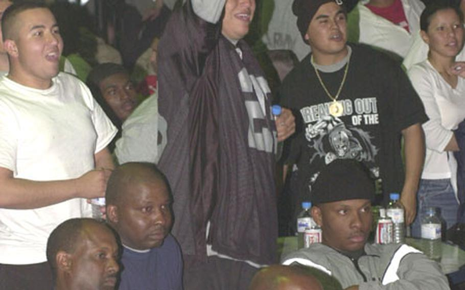 Raiders fans at Camp Doha, Kuwait, cheer on their team during Super Bowl XXXVII early Monday morning.