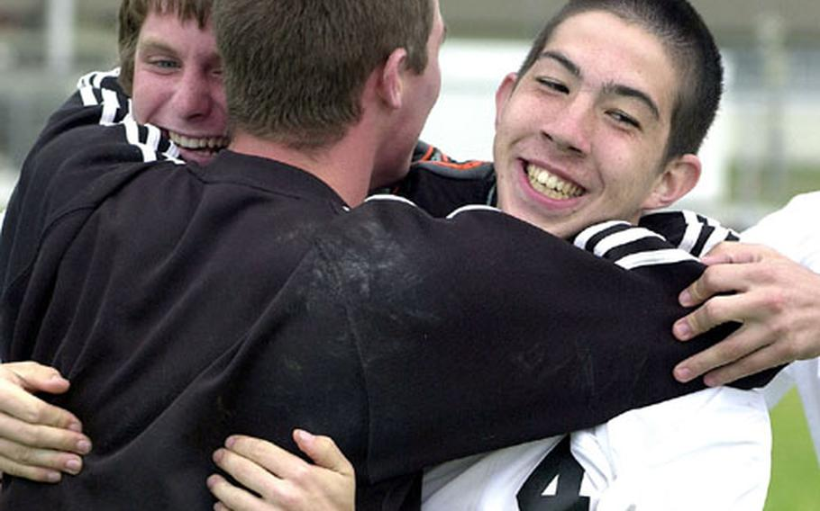 Nick Riegel, Chris Riegel and Jonathan Leach (4) of Matthew C. Perry celebrate their penalty-kick shootout victory over the Osan American.