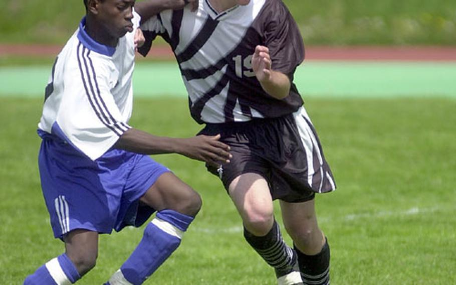 Hohenfels' Fredner Reserve, left, and Baumholder's Scott Hull vie for position during a DODDS high school soccer game in Baumholder, Germany, on Saturday.