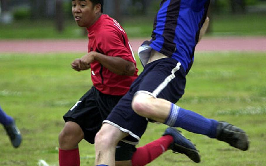 Luke Cummings, right, of the Christian Academy In Japan Knights readies to boot the ball as Ace Ranada of the Nile C. Kinnick Red Devils defends during Friday's quarterfinal of the Department of Defense Dependents Schools-Japan boys soccer tournament at Bonk Field, Yokota Air Base, Japan.
