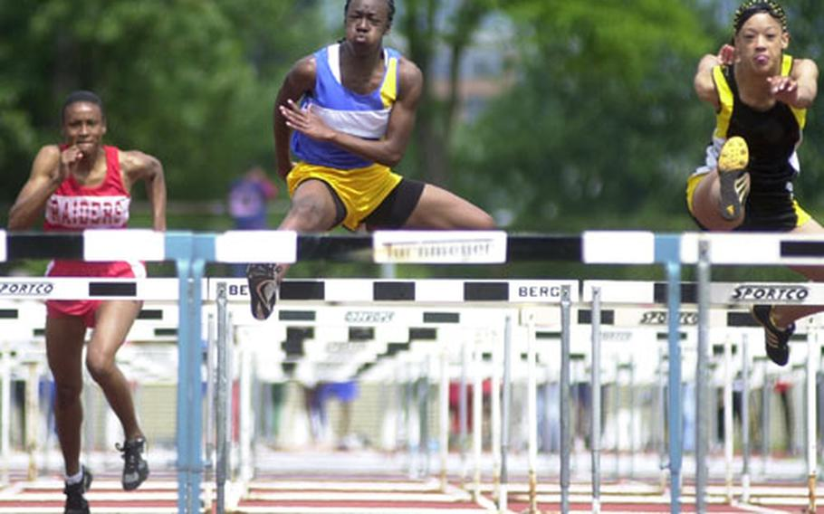 From right, Hanau's Jennifer Cain, and Ansbach's Brittney Britton race for first place as Kaiserslautern's Shanara Collins falls behind during the 100-meter hurdles at the DODDS Division I Track and Field Championships in Wiesbaden, Germany, on Saturday.