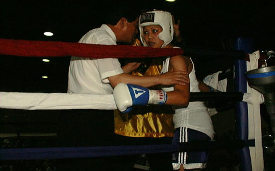 The referee checks the condition of Sgt. Cynthia Nava of 168th Medical Battalion during her bout with Sgt. Camille Adams of 169th Signal Company. Both were on a nine-bout July 4th holiday boxing card put on by Army at Camp Walker in Taegu, South Korea.