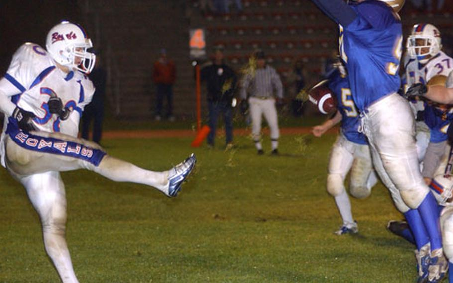 Punting from the back of his own end zone, Ramstein punter Austin Izzo, left, narrowly gets the kick past a leaping Scott Pangrazzi of Wiesbaden in the fourth quarter of the DODDS Division I Football Championship game in Baumholder, Germany, on Saturday.