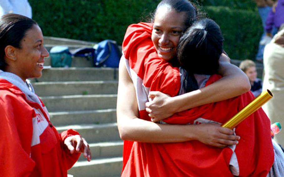 Kaiserslautern High School 1,600 sprint medley runners Mandra Smith, left, and Dupe Babatunde, right, congratulate teammate Cassie Freeman after her final sprint gave the Raiders the gold medal.