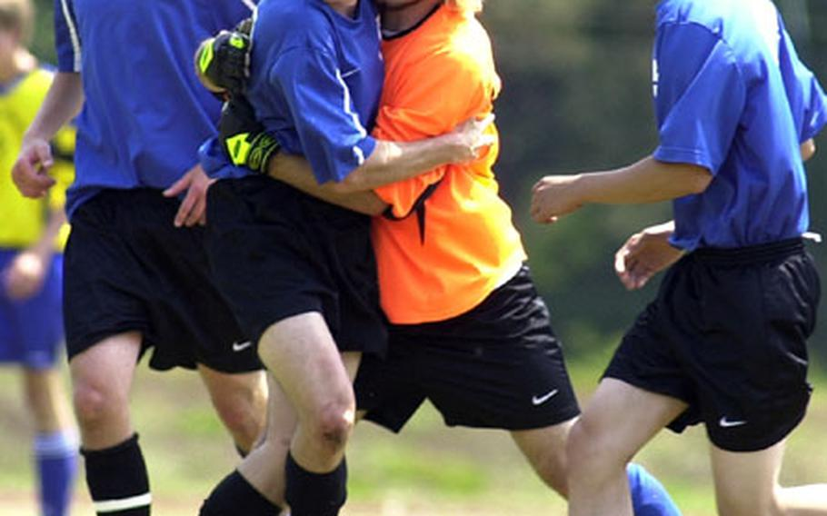 London Central goalie Mark Pierce, third from left, congratulates Seth Hansen on his first-half goal against Bamberg on the opening day action of the 2004 DODDS-Europe soccer championships in Ramstein, Germany, on Thursday.