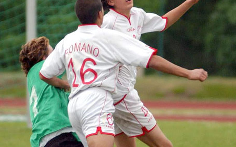 From left, Naples' Daniel Rubia is knocked down by American Overseas School of Rome's Dario Romano as Juan Pablo Gomez Guarte heads the ball during the DODDS European Division III boys' soccer championship in Kaiserslautern, Germany, on Friday.