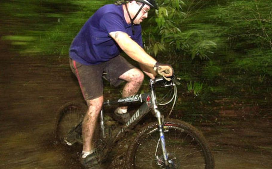 Staff Sgt. Matt Butts take a mud puddle in the 14th Tour de Tama mountain bike race at Tama Hills Saturday.