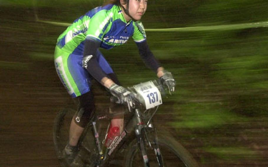 Sachiko Takeda rides her bike through the muddy course of the Tour de Tama at Tama Hills Saturday.