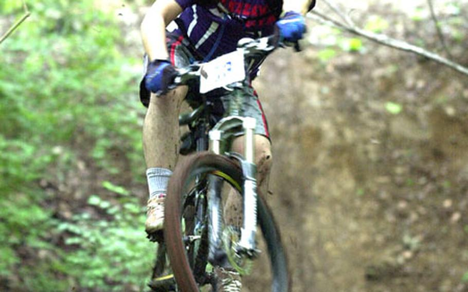 Nobuhisa Okada gets some air on the muddy trails of the Tour de Tama Saturday.