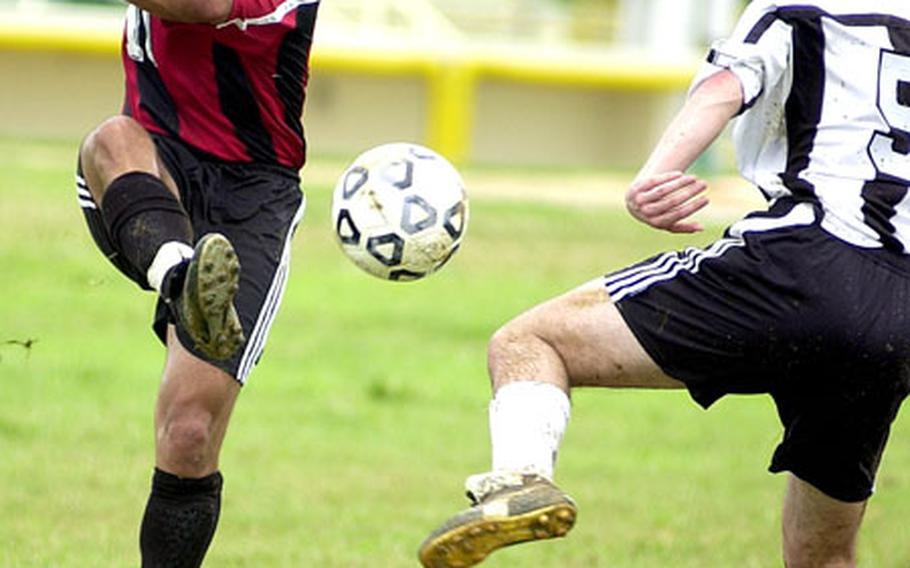 Brian White, left, of Marine Corps Base Hawaii boots the ball past Austin Brennaman of Japan's Iwakuni Air Station during Monday's pool play in the 2004 Marine Forces Pacific Regional Soccer Tournament. Two-time defending champion Hawaii rallied from a 1-0 deficit to beat Iwakuni 4-1.