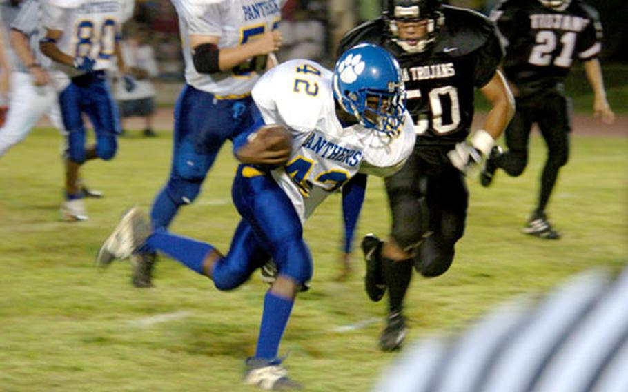 Yokota Panthers sophomore Anthony McNeil evades the Zama Trojans defense during a run for the first touchdown of Yokota's victory Friday night at Yokota Air Base, Japan.