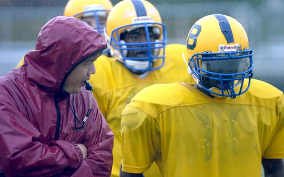 Bamberg head coach Jim Davis talks with T'Andre Stuckey during special teams practice in Bamberg, Germany, on Monday. Behind Stuckey are Brian Thames and Riley Livingston.