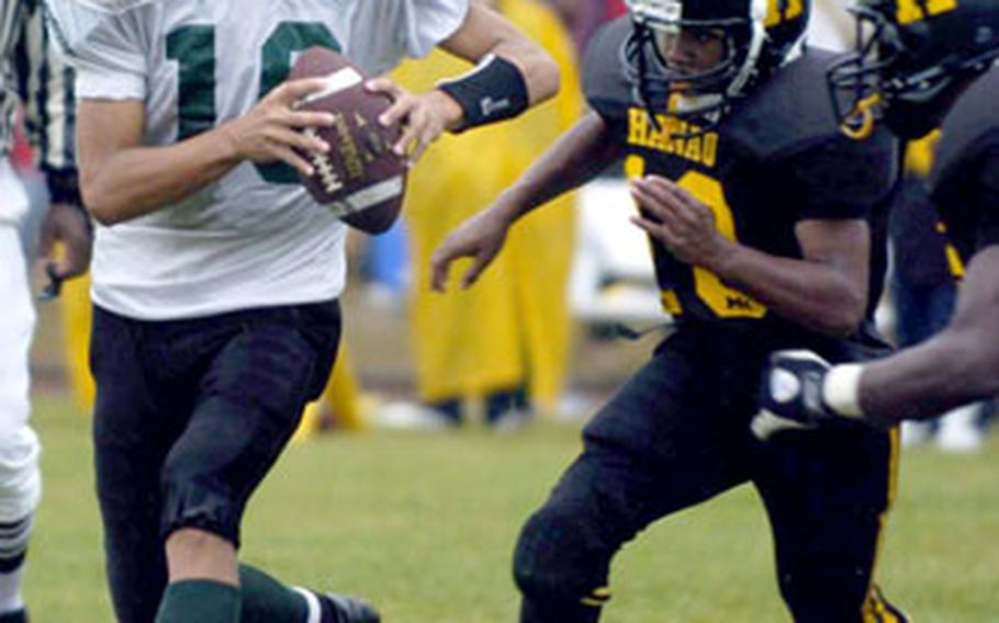 Naples quarterback Tyler Terronez is pressured by Hanau's Andrew King, center, and Perry Ronderio.