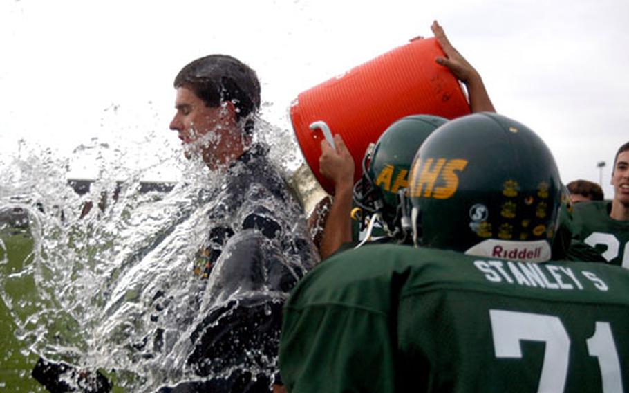 Alconbury football players dump water over head coach Ron Behr after the team won its first game since the start of the 2001 season, beating Brussels 52-36. It was also Alconbury's homecoming game.