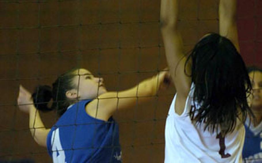 Hohenfels' Vanessa Velez, left, tries to spike the ball past Baumholder's Kandi Dyer.