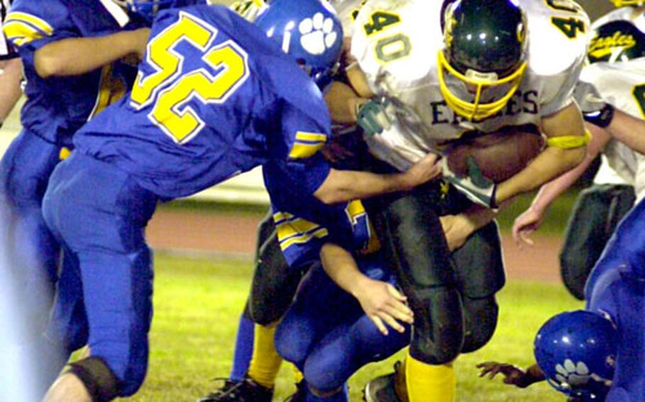 Robert D. Edgren ballcarrier Kevin McDonald (40) is surrounded by the Yokota Panthers defense during Friday's game at Yokota Air Base, Japan. Yokota routed Edgren to clinch its seventh straight JFL title.