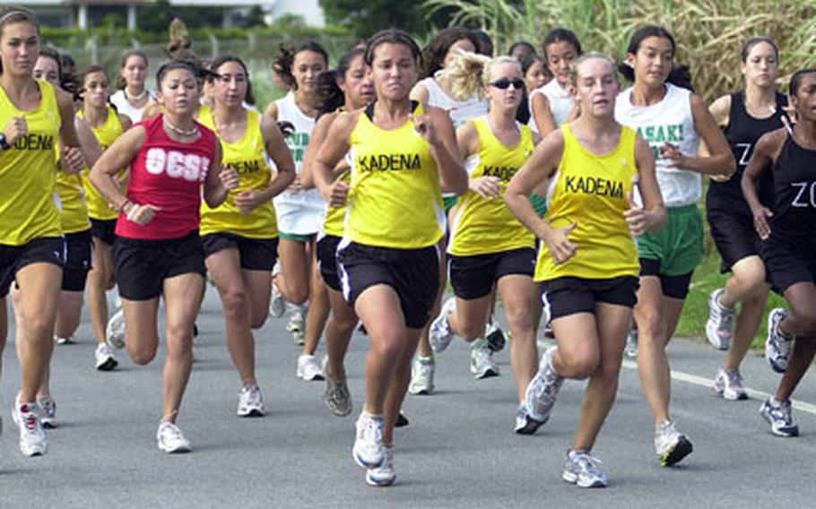 Dianne Abel, center, of Kadena Panthers and teammate Taylor Carver, just to her left, lead the pack past a sugar cane field near Torii Beach at the start of Wednesday's Okinawa Activities Council all-island cross-country championship girls 3.1-mile individual race at Torii Station, Okinawa.