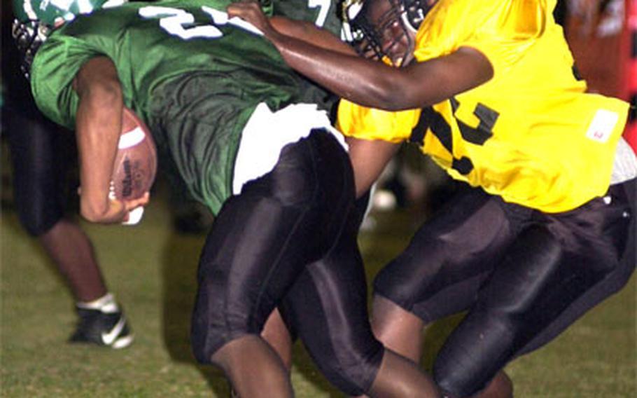 Kubasaki's Lenard White (26) gets dragged down by Dominique Jernigan (72) of the Kadena Panthers.