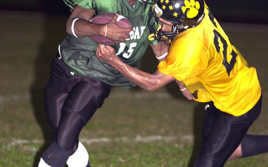 Kubasaki Dragons quarterback Michael Dickerson (15) tries to elude the grasp of Kadena Panthers defender Josbie Morris (23).