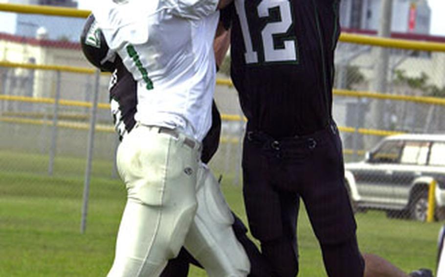Kadena Dragons safety Michael Soster, right, intercepts a pass intended for Courtney-Hansen Titans receiver Trevor Highsmith.