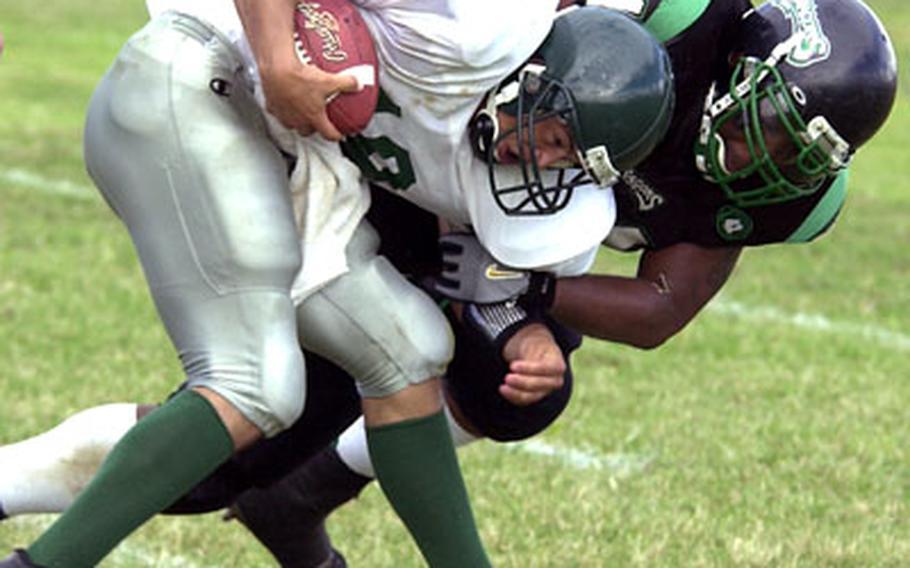 Courtney-Hansen quarterback Juan Garcia is brought down by Kadena defender Leonard Simmons.