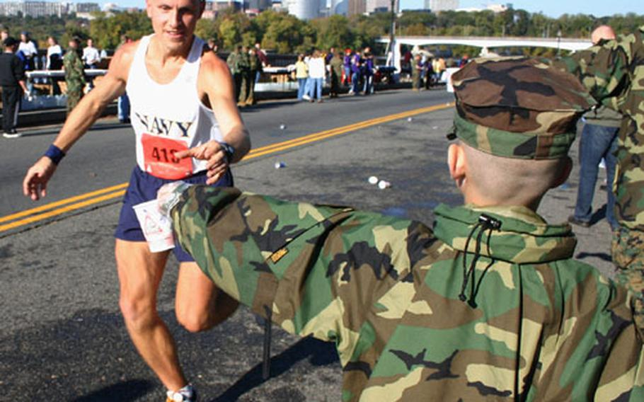 Marine Corps Marathon runner Eric Makovsky of Hanover, Md., grabs a cup of water from eight-year-old Matthew Rupert at a water station near the Lincoln Memorial during Sunday's race in Washington.