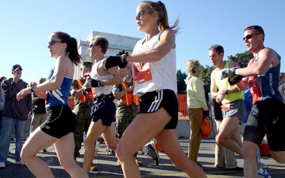 Runners check their splits as the pass the 10-mile mark at the Lincoln Memorial during in Sunday's Marine Corps Marathon.
