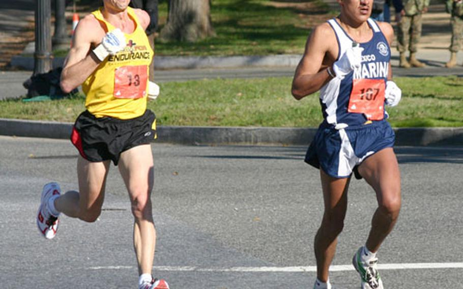 Ruben Garcia, a Mexican sailor, leads Carl Rundell of Birmingham, Mich., toward the 15-mile mark of Sunday's Marine Corps Marathon. Garcia won the race in 2 hours, 22 minutes and 14 seconds, nine seconds ahead of runner-up Rundell.