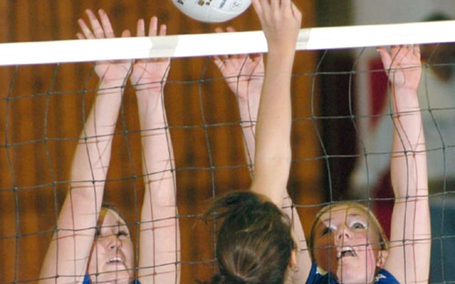 Lajes' Colleen Koonst, left, and sister Alaina Koonst leap to block the shot of Brussels' Christine Exner during a quarterfinal game against Brussels.
