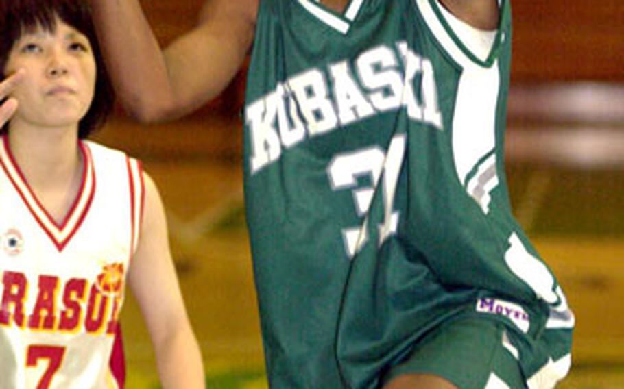 Kubasaki freshman Danielle Robinson goes up for a shot past an Urasoe defender during Friday's girls basketball contest. Urasoe beat the Dragons 63-38.