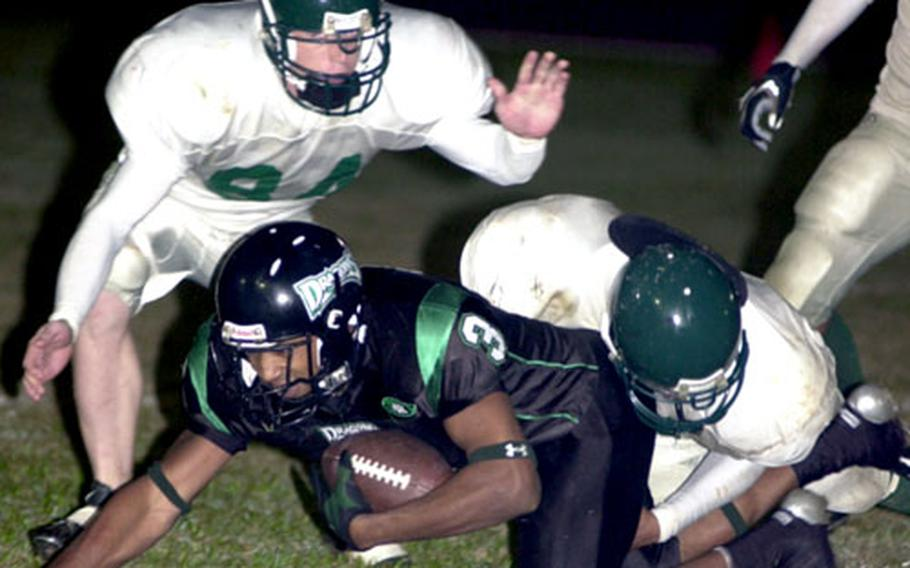 Kadena Dragons receiver Tarrick Jackson is wrestled down by defenders Andrew Cimonetti and Stephen Ellis of the Courtney-Hansen Titans. Jackson caught 4 passes for 66 yards and a touchdown.