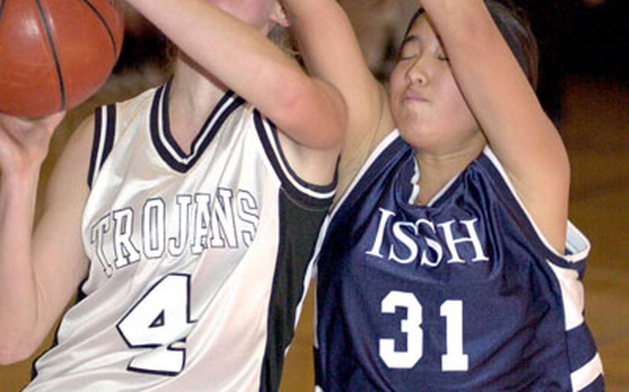 Zama American Trojans senior Kate Shicks (4) is fouled by Nako Nakatsuka of the International School of the Sacred Heart.