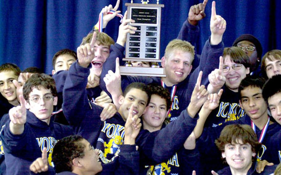 Members of the Yokota Panthers wrestling team celebrate their DODDS-Japan championship on Saturday. Yokota won five individual weight-class gold medals and outscored second-place Nile C. Kinnick 55-50.