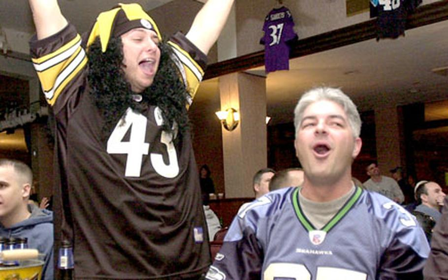 Pittsburgh Steelers fan Air Force Staff Sgt. Erik Marsaln, left, celebrates at Kadena Air Base Rocker NCO club after the officials reviewed and upheld Pittsburgh's first touchdown of the Super Bowl while Seattle fan Bill Hafemeister, right, boos the referee's decision.