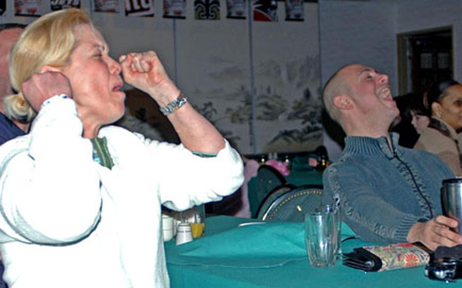 Lt. Cmdr. Lisa Braun, a Seattle Seahawks fan, shows her disappointment after a Seahawks turnover, while Steelers fan Petty Officer 1st Class Don Acker, right, cheers. About 250 members of the base community watched the game in the Harbor View Club at Sasebo Naval Base.