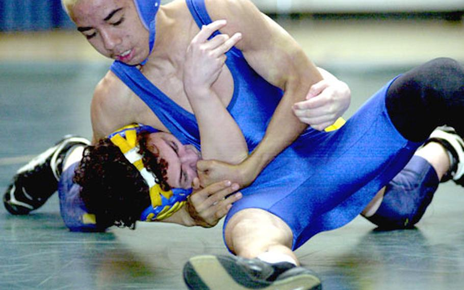 Dylan Pablo of Guam High gets Mark Meade of Yokota in a head-in-arm hold during Thursday's 101-pound round-robin bout. Pablo decisioned Meade 2-0.