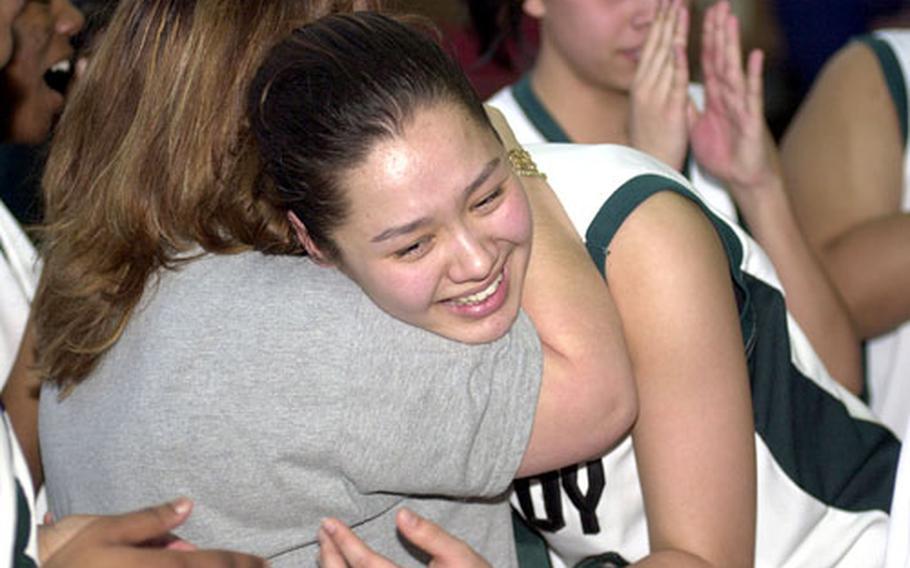 Taegu American senior center Kelli Cox gets a hug from coach Michelle Chandler after Thursday's win over Faith Academy.