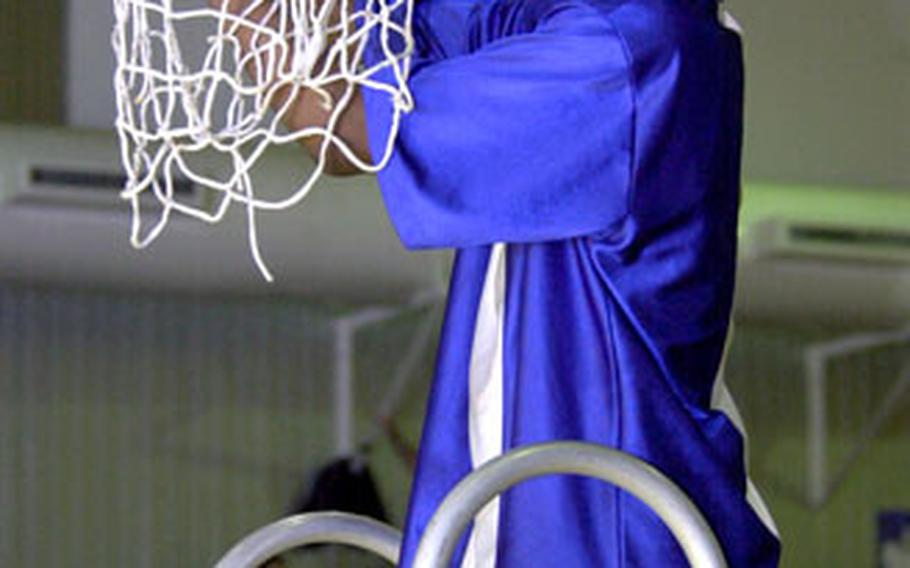 Yokota's Caiveon Thomas cuts off a piece of the net after his team beat Seoul American 72-51 to take the Far East Boys Class AA title on Kadena Air Base, Okinawa, on Saturday.