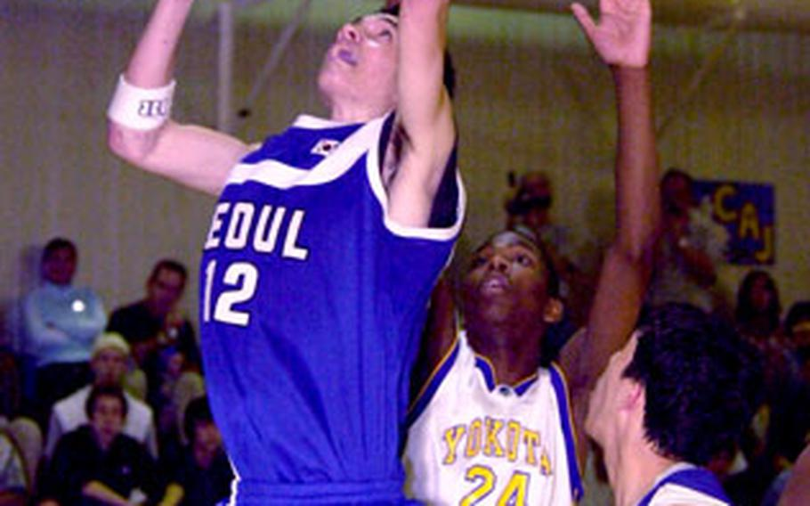 Seoul American's Jeremy Christopher puts up a shot as Yokota's Caiveon Thomas attempts to block.