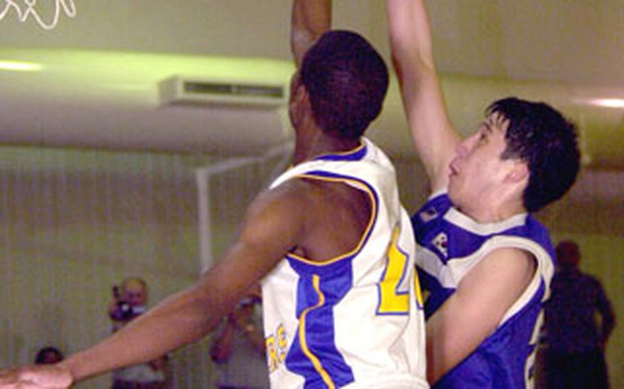 Seoul American's Andrew Luna, right, puts up a shot just out of Yokota's Caiveon Thomas.