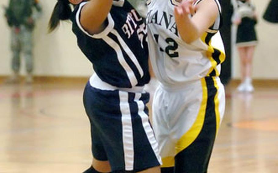 Bitburg's Melissa James, left, blocks a pass by Hanau's Feiloaiga Oloi during the DODDS Europe Division II girls championship in Mannheim, Germany, on Saturday night. Bitburg upset top-seeded Hanau 45-31 to win the title.