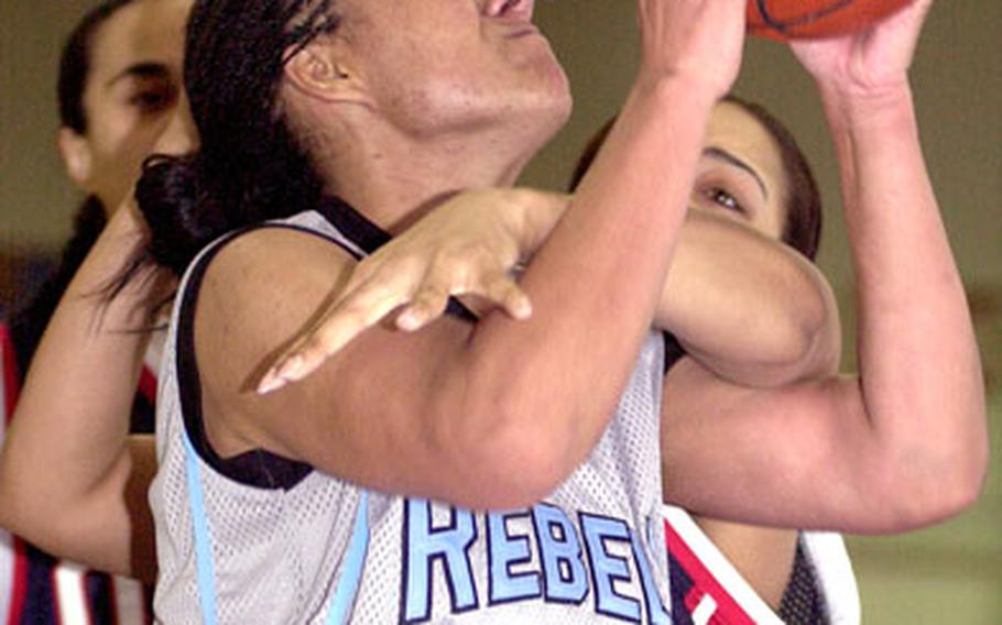 Ebony Irving of the Yongsan Runnin' Rebels is fouled by Charlene Alexander of the Osan Defenders during Sunday's women's championship game in the 2006 Koreawide post-level basketball tournament on Yongsan Garrison, South Korea. Yongsan edged Osan 65-63.
