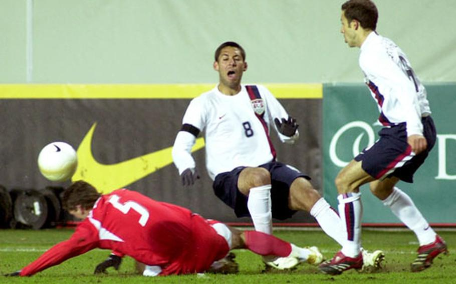 Poland's Arkadiusz Radomski, left, makes a hard tackle against Clint Dempsey of the U.S. team during Wednesday's World Cup warmup at the Fritz-Walter-Stadion in Kaiserslautern, Germany. At right is Steve Cherundolo.