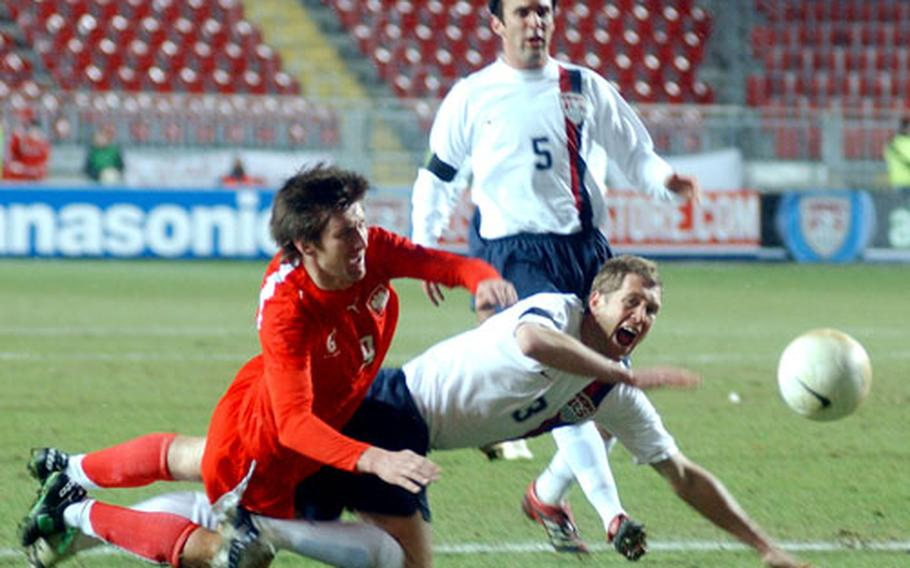Poland's Grzegorz Rasiak, left, gets tangled up with Gregg Berhalter of the U.S. as Kerry Zavagnin watches.