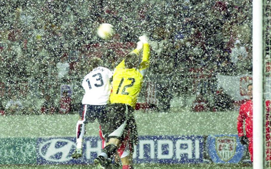 Taylor Twellman of the United States and Poland goalie Artur Boruc go up for a ball in the driving snow during the second half.